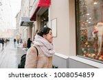 girl looks at storefront   Shutterstock . vector #1008054859