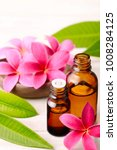 Small photo of Frangipani Absolute Oil and red plumeria flowers on the wooden table