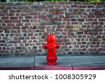 a deep red fire hydrant sits in ...