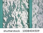 Small photo of snow adhered to the grid of the fence