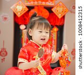 "Small photo of Chinese baby girl with traditional dressing up and ""FU"" means ""lucky"" greeting card.some ""FU"" means ""lucky""greeting card on the wall as well"