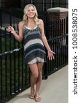 Small photo of Stunning young blonde woman laughs as she stands in a black and white sundress or romper near a cast iron fence