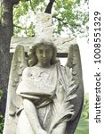 Small photo of View of statue of an angel against dark foliage background. Dramatic unusual scene of statue angel as a symbol of the end of life and afterlife.