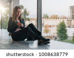 young woman sits on floor near... | Shutterstock . vector #1008638779