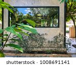 Small photo of Exterior boxlike decorative space. Concrete and black aluminum window frame, surrounding with tropical green natural atmosphere. Architecture idea concept. Loft style.