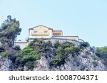 Small photo of Daylight view to rock mountains with green trees and modern house on top. Bright blue clear sky. Negative copy space, place for text. Cap d'Ail, France