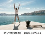 carefree woman jumping at beach.... | Shutterstock . vector #1008789181