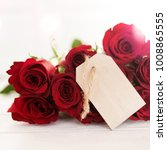 Small photo of Bouquet of red roses with a label to describe on a tender white background