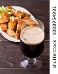Small photo of Glass of dark beer and siracha buffalo chicken wings. Ale and food