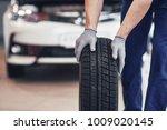 mechanic holding a tire tire at ...   Shutterstock . vector #1009020145