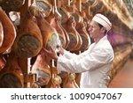 in a ham factory  a man in... | Shutterstock . vector #1009047067