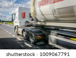 truck whizzing by on a sunny... | Shutterstock . vector #1009067791
