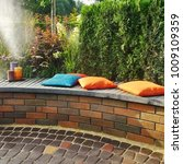 Small photo of Modern Backyard Patio And Party Area On Backyard Garden. Family Corner For Relaxation And Rest On Wooden And Brick Rounded Bench With Pillows
