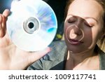 woman holds dvd up to the sun | Shutterstock . vector #1009117741