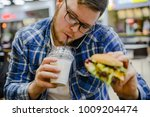 man eat burger drink milk shake ... | Shutterstock . vector #1009204474