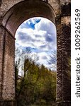 Small photo of View through One of the Bock Casement Arches into the Medieval Village of Grund with Trees Blooming in Spring in Luxembourg City, Luxembourg