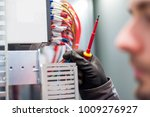Closeup of electrician engineer works with electric cable wires of fuse switch box. Electrical equipment - stock photo