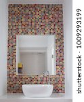 Small photo of Bathroom wash basin with colorful glass mosaic tiles and mirror inset into the tiles