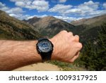 Small photo of Mans arm with Sportswatch showing altitude with altimeter in the mountains while hiking and climbing with purposely blurred mountain background