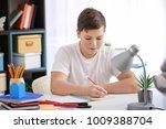 teenage boy doing homework at... | Shutterstock . vector #1009388704