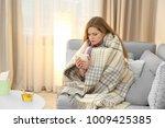 sick woman wrapped in warm... | Shutterstock . vector #1009425385