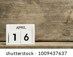 White block calendar present date 16 and month April on wood background