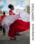 Small photo of Quito, Ecuador 4/28/2017 parade celebration for culture day, a young unknown african Ecuadorian dances with traditional clothes in city center on the street and people photograph her in city center