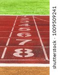 Small photo of Running track lines with green grass. running track. Stadium track.