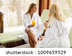 two cheerful women in bathrobes ... | Shutterstock . vector #1009659529