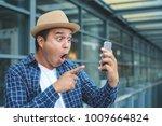 asian man looking smartphone... | Shutterstock . vector #1009664824