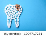 Small photo of Sugar destroys the tooth enamel and leads to tooth decay. Sugar cubes are laid out in the form of a tooth and brown sugar symbolizes caries. Copy space for text