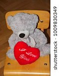 "Small photo of Grey Teddy bear is sitting on the wooden chair with plush heart with ""I Love You"" on it."
