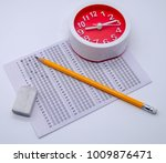 Small photo of Answers sheet with yellow sharp pencil, clock and rubber isolated on white background. Top view of them. Take the exam timely concept.