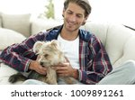 Stock photo handsome guy with a dog sitting in a large armchair 1009891261