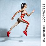 Small photo of Sporty woman runner in fashionable sportswear on grey background. Dynamic movement. Side view