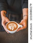 Small photo of Barista presents milk foam art of Native American with headdress on a Cafe Mocha, a free pour with light etch