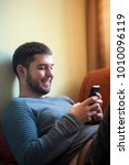 Small photo of Young handsome man sitting on a sofa, typing a text message, a reply to his friend, enjoying some leisure time