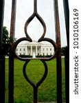 Small photo of Washington DC. USA, 22nd June, 2012 The White House as seen through the exact middle of the iron fence that surrounds the grounds.