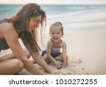 mom and happy baby playing near ... | Shutterstock . vector #1010272255
