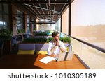 Small photo of Inventory strategist solving problems and using laptop at cafe table. Clever hardworking man dressed in white shirt working with papers. Concept of analyzing model forecast to design contingency pla