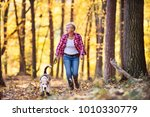 Stock photo senior woman with dog on a walk in an autumn forest 1010330779