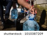 collecting natural spring water ... | Shutterstock . vector #1010387209