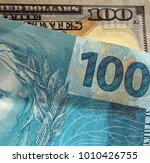 Small photo of Hundred dollars and a hundred reais currency brazilian note and usa currency money