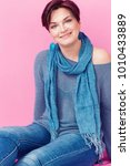 Small photo of Beautiful woman portrait smiling while wearing blue sweater, scarf and dangle earrings