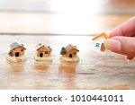 Small photo of Hand choosing mini house model. Planning to buy property. Choose what's the best.