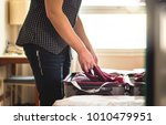 packing suitcase in hotel room. ... | Shutterstock . vector #1010479951