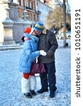 Small photo of Adult man and adult woman kissing in a winter city. Vertical shot.