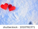 two red hearts on a snowy...   Shutterstock . vector #1010781571