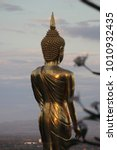 """Small photo of """"Nan, Thailand - Wat Phra That Kao Noi at Nan, Thailand. Nan province with Buddha statue on Mountaintop in sunrise"""" ,Golden Buddha standing on a mountain in sunrise"""