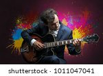 Small photo of Young classical guitarist musician with colorful splotch wallpaper